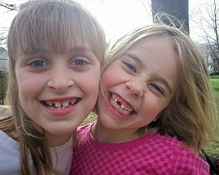 CAITLIN PERRY (left) and AIDAN MCDANEL compare smiles and missing teeth on their street in Poland Township.