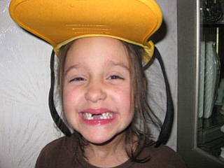"SKYLER HUDA, a first-grader at Dobbins Elementary School in Poland, stopped at Nana and Papa DeLuca's home in Struthers to show off her ""Goofy"" hat and missing teeth. She had just gotten back from a Disney cruise with her parents and brother."