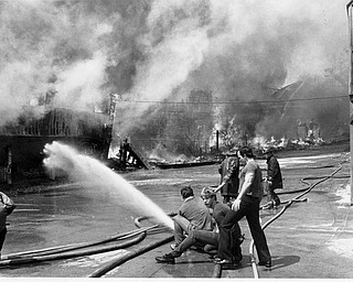 Apr. 26, 1984 Firefighters try to thold the line and keep the flames from moving to the carousel (seen at far right).