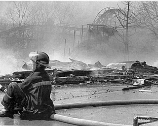 Apr. 26, 1984 A youngstown City Fireman siits on a hose as part of the Wild Cat roller coaster goes up in flames. The 90 year old Idora park went up in flames, destroying the Lost river, park offices and and a row of concessions stands. The two -allarm fire sent one fire fighter to the hospital.