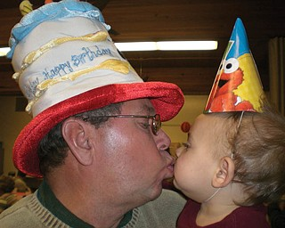JIM DORMAN of Boardman shares a kiss with his grandson, Peter Koulianos of Campbell, on their joint birthday. Nov. 11.
