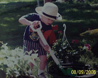 BRYAN is the grandson of Judith Ferrett of Hubbard. He's wearing his Amish hat while planning flowers.