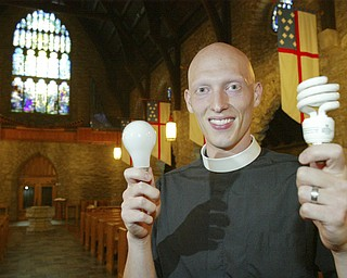Rev. Jeremiah Williamson, assistant pastor at St. John Episcopal Church in Youngstown holds an incandesant buld in one hand and a flourescent in the other. The church is replacing incandesant bulbs with flourescent to save energy. William D. Lewis / The Vindicator