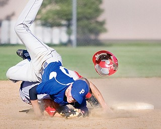 Poland's Phil Lipari (10) lands on top of Niles' Nick Harper (1) after making the catch at second base where Harper was called out ending the top of the seventh inning at Cene Field in Struthers on Monday evening.