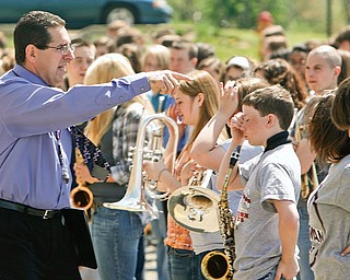 """Boardman director of bands Thomas Ruggieri moves the band members into position as they will stand in position to """"script out 100."""""""