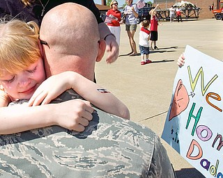 8-year-old Tayla Jones of New Waterford hugs her father John with his son Jonathan, 6, on the right holding a sign.
