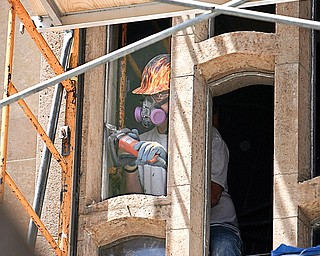Steve Yates of Kansas and Bovard Studio Inc, of Iowa.. works on the grout as the stained glass windows are removed - and restored and replaced - at the Cathedral on Wood St.