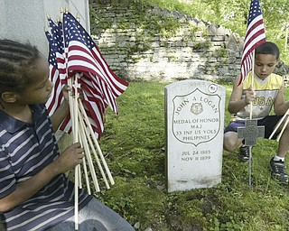 K'emonie Colpetro, 9, places a flag on the grave of Maj. John A. Logan in Oak Hill Cemetery, Youngstown. Looking on is Larenz Rhodes, 8. Both boys are members of a youth group at American Legion Post 732 in Youngstown helping decorate graves at Oak Hill Cemetery . Maj Logan is the son of General John A. Logan who issued General Order 11 at the end of the Civil War resulting in Decoration Day and then Memorial Day.