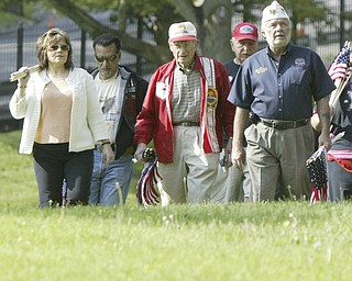JP Brown III, right of Boardman, a Navy veteran and former Amvets National Commander leads a group of veterans and volunteers as they place flags on graves of veterans in Oak Hill Cemetery in Youngstown, Oh. From left others are Karen Brandt, Ed Romero and Raymond Braidich.