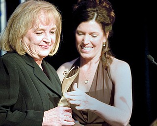 Patricia Brozik, President of Community Foundation of the Mahoning Valley, receives the Athena Award from Dr. Sheryl Figliano, from Centers for Hearing Care at Mr. Anthony's on Thursday evening.