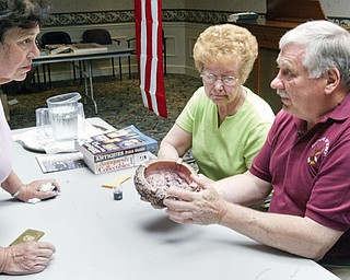 Dahlia Clemen of Liberty, left, looks on as auctioneer Marcel Ulrich of McDonald evaluates an antique ashtray  for her during an event Friday at Shepherd of the Valley in Howland. Next to Ulrich is a friend of Ulrich's Delores Kale of Warren.