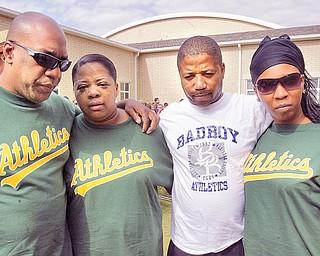The family of Lloyd McCoy Jr., a 6th grade shooting victim, embrace during a ceremony at Willard School in Warren Friday where he was a student. From left to right, they are his father, Lloyd McCoy Sr., his mother, Pamela McCoy, uncle David Williams and sister Brittnay McCoy.