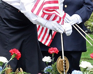 Firefighter/EMT Lee Ann Setser places a flag during the Memorial Day services Sunday afternoon in McDonald.