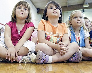 C.H. Campbell Elementary School kindergarten students, from left to right, Eliza Blasko, Emma Conroy and Lily Grdic watch during an Arbor Day program at their school Thursday in Canfield.