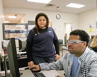 Leon Hopkins of Youngstown looks for work at Mahoning County One Stop in Boardman. With him is Arelis Laviena, One Sop Facilitator.