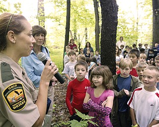 ODNR Division of Wildlife Officer Jamey Graham, left, speaks during a dedication of Wild School Site at Poland Union Eelm. School Tuesday. Next to her is Poland Union 2nd grade teacher Linda Watts. Students gathered outside the school for the dedication.