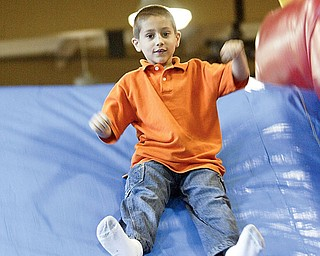 First grader Nicholas Boyarko of C.H. Campbell in Canfield  runs through bounce course at the school Friday as part of end of year festivities.