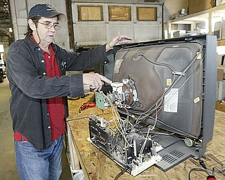 Val-e-Tronics owner Gary Piskor, prepares to disassemble an old analog TV set at his Mahoning Ave site in Youngstown. They disassemble and recycle TV's and computers.