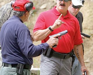 Glock Staff Instructor Joel Hodges of Florida explains technique to  Robert Paterniti.