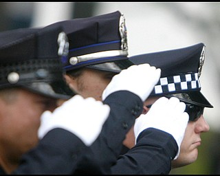 Hubbard police officers salute as Army Chief Warrant Officer S. Blane Hepfner  is laid to rest at Hubbard Union Cemetery.