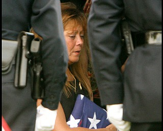 Framed by honor guards  Renee Possert  holds the flag as Army Chief Warrant Officer S. Blane Hepfner  is laid to rest at Hubbard Union Cemetery.