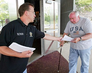 UAW 1112 shop chairman Bob Marstellar passes out information to GM/UAW retiree Larry Ayers of Austintown outside Metroplex Hotel in Liberty Tuesday. More than 1,500 retirees attended the meeting to find out details of health care plan.