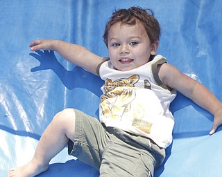 Colton Huff (21 mths) of Cortland glides down an inflatable slide/play area at the Mahoning Valley Rib Burnoff Saturday June 27, 2009