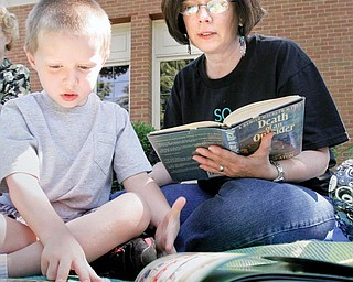 Carol Genova and her grandson Colin Genova, 5, of Niles, participate in a read-in at the main library in Warren Monday to bring attention to proposed library funding cuts.