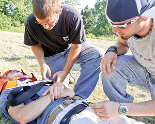 """HOW IT'S DONE: Jace Melick, left, of Boardman and Brian VanDyke of McDonald strap Anthony Pilolli of Berlin Center on a stretcher as Pilolli plays the role of """"patient"""" during an extrication exercise with Liberty Fire Department. Capt. Bill Opsitnik led the hands-on exercise for students in the emergency medical technician program at Youngstown State University."""