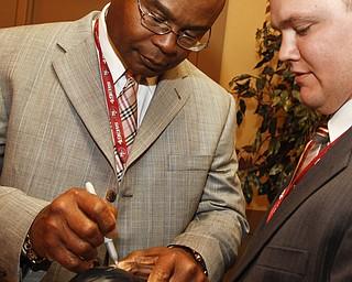San Francisco 49ers coach Michael Singletary signs a mini helmet for Joe Kilgore (26) of Columbiana at Leo's Ristorante in Warren, Monday June 29, 2009Lisa-Ann Ishihara