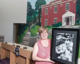 framed work: Kathryn Infante of Liberty displays one of her photographs, the undercarriage of a truck, which has been featured in the display of artwork by residents at the township administration building, 1315 Church Hill-Hubbard Road. She's in the meeting room at the administration building. The current display shows peonies by Infante and acrylics featuring various subjects by Tim Micklas.