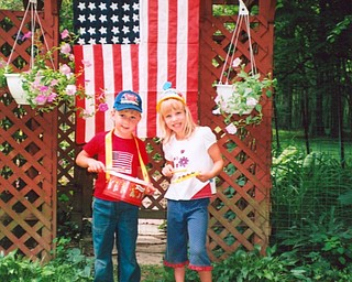 """David and Lee Culp sent this picture of their grandkids, Robbie and Kassie Williamson, taken last year on the Fourth of July. They noted that the hand-sewn flag has 48 stars and was given to them by a treasured """"senior"""" friend."""