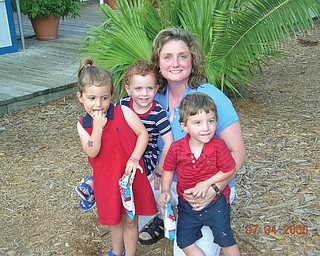 Erin Angelo of Canfield is surrounded by her triplets, Sydney, Madison and Trey, during a family vacation to Hilton Head Island in 2006.