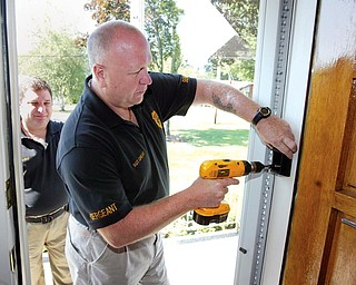 Liberty Police Department Sgt. Robert Graef installs a lock box at resident's home as part of Senior Watch Program. At left is Librty Police Capt. Toby Meloro.