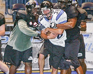 Former YSU quarterback Tom Zetts is wrapped up by defense during af2 Mahoning Valley Thunder practice.