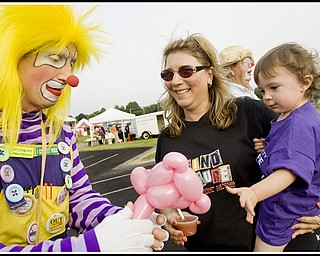 """7.10.2009 Gianna Bindas, 1, wears the purple shirt signifying a cancer survivor, while being held by her mother, Michelle Bindas, both of Poland, and receiving a balloon animal from """"Woodee"""" the Clown, also known as Joe Humansky, of Columbiana, during the Relay For Life at Poland's High School Stadium on Friday evening. Diagnosed at 9 months with a Wilms Tumor, Gianna has since had surgery, 21 weeks of chemotherapy, and despite loosing a kidney, her parents say she is """"doing real good."""" Geoffrey Hauschild"""