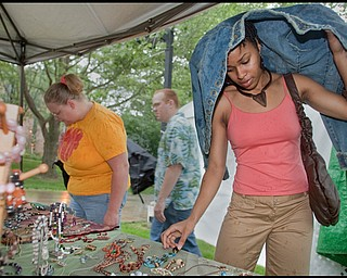 """7.11.2009 YSU student, Darcelle Formby, hides from the rain beneath her jacket while looking at jewelry from Madison OH resident, Kim Mizerak's """"A Vintage Advantage Jewelry"""" booth on YSU campus during the YSU Festival of the Arts on Saturday afternoon. """"I'd never been to the festival before so I thought I'd check it out,"""" Formby said. Geoffrey Hauschild"""
