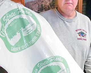 Billdunlap, an employee of Beaver Creek tate Park displays trashbags provided to park visitors. The park is in hte 2nd year of a carry out your trash program. wd lewis