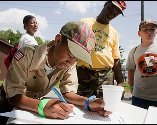 7.16.2009 Christian Thornton, of Pack 388 in South Euclid OH, adds his signature to those of others who have seen the 100 year commemorative mural traveling to all Scout Camps across the country while at Camp Stambaugh on Thursday afternoon. Geoffrey Hauschild