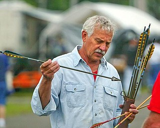 Tom Nega of Apollo, Pa. looks over an archery arrow at Dave and Ed's Swap Meet Friday at the Canfield Fairgrounds. Nega is an avid bow hunter and likes the antique arrows.