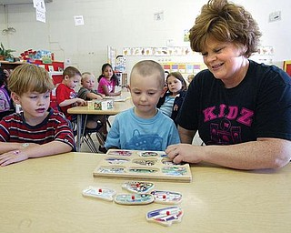 EARLY LEARNING: Theresa Herrick, co-owner of the Kidz Kastle preschool in Girard, helps pupils, Christopher Glunt, 5, left, and Mason Day, 3, with a puzzle. Herrick lamented the abolition of the state's Early Learning Initiative program due to budget constraints.