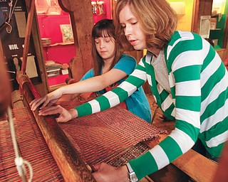 """Working the old loom are Anastasia Monrean of Liiberty, 11, and the director Rebecca Whitenberger at the Mahoning Valley Historical Society's """"Pioneer Days"""" Summer Camp."""