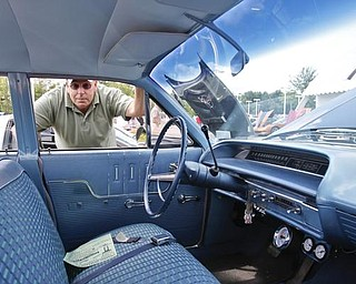 Rick Jenkins of Espyville, PA peers through the driver side window of his 1963 Chevy Bel Air Station Wagon during the collaborative car show with the  Mahoning Valley Corvettes and Greenwood Chevrolet in Austintown, Sunday July 19, 2009 Lisa-Ann Ishihara