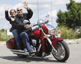 Todd and Mary Chuey of Hubbard wave to their friend as they start off their ride to raise money for several local charities, based at Harley Davidson Biketown in Austintown, SundayJuly 19 2009Lisa-Ann Ishihara