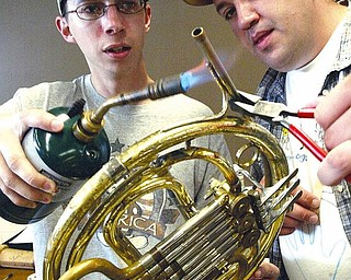 Derrick Kittle, left, and Franklin Stout, both students at Youngstown State University, work on a French horn during an instrument-repair class in Bliss Hall on campus. Students learned to solder instruments Wednesday.