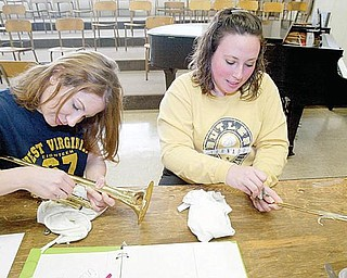 Krista Ferry, left, and Shanna Kelly clean the areas they plan to solder back together on a trumpet in the instrument-repair class.