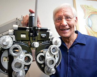 Optometrist Dr. John J. Guerriero of Boardman stands next to a phoropter, an instrument used during eye examinations to determine eyeglass prescriptions. Dr. Guerriero has been in practice 50 years this month, starting in 1959 in Warren, and opening an office on Canfield Road in Cornersburg two years later.