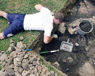 DIGGING DEEP: Joe Paloski, a graduate student at Youngstown State University, digs in a pit outside on the site of the former jail outside the old courthouse on Court Street in Canfield. The purpose of the dig was to explore the area's history.