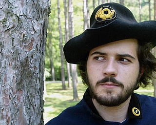 YOUNG GUN: Having spent more than half of his life re-enacting battles of the Civil War, Grant Kirkwood, 21, of Liberty, wathces over his Union camp. Kirkwood has participated in re-enactments for 16 years.