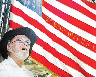 FLAGS OF OUR FATHERS: Jack Schinness, 73, of Chardon, stands in front of a Union flag embroidered with the text of the 7th Regiment of the Ohio Volunteer Infantry. Schinness is one of more than 200 volunteers who will perform in a Civil War re-enactment at Beaver Creek State Park in Columbiana County this weekend.